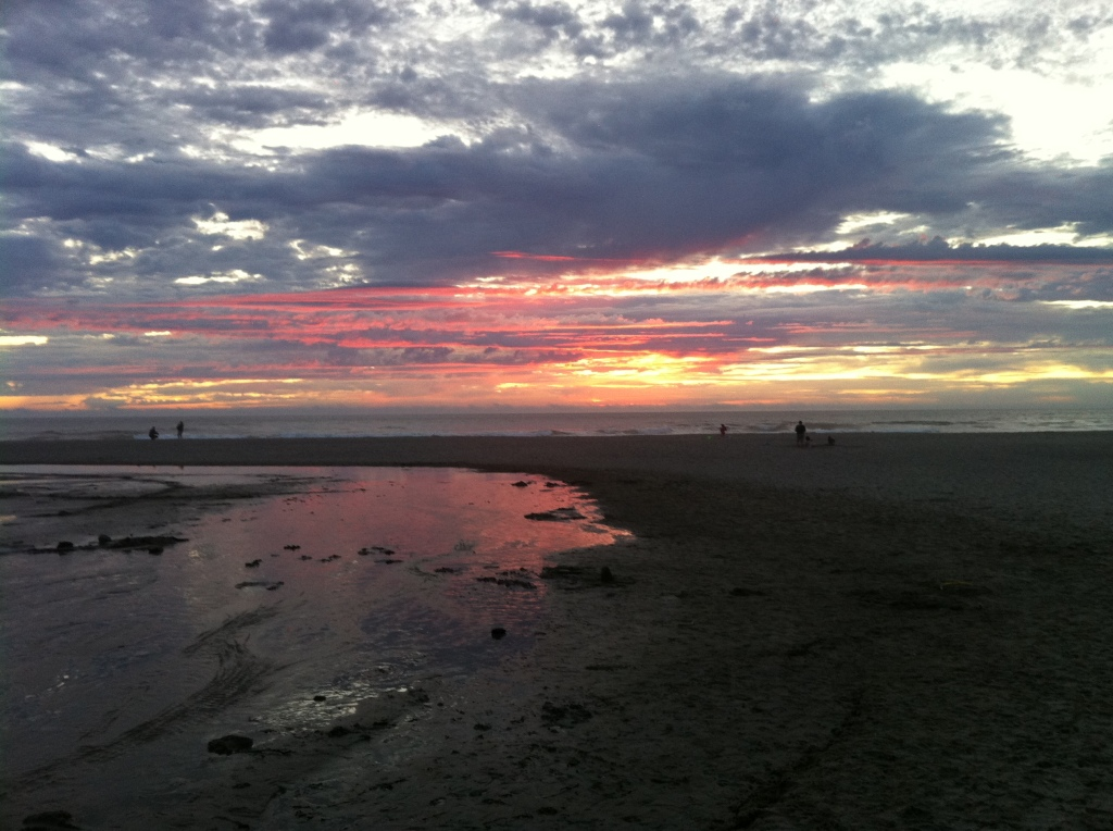 Oregon last at sunset with pink and yellow and dark sky over beach at dusk