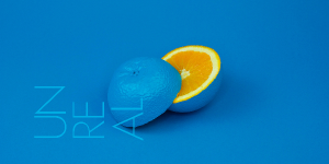Announcement for UNREAL reading at Antigone Books, featuring blue text over blue background and an orange painted blue but sliced to reveal the color orange inside