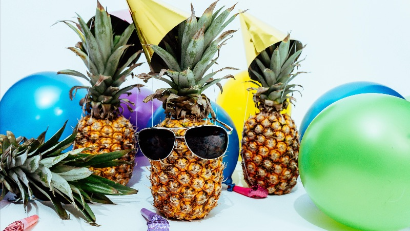 Image of pineapples, one of them with sunglasses on, with party hats on at a party with balloons and party horns.